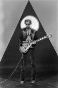 Peter Banks, guitarist for Yes, plays guitar against a backdrop of a triangle and a large circular light. Los Angleles. ca. 1970s Los Angeles, California, USA
