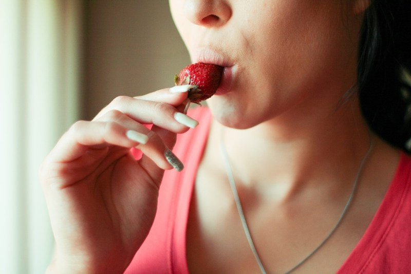 Close up of a lady eating a strawberry in a seductive manner