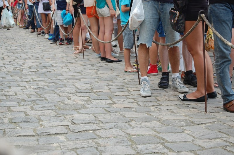 Medium to long shot of people queueing for an event
