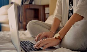 Feature image of a blogger on a hotel bed with a laptop