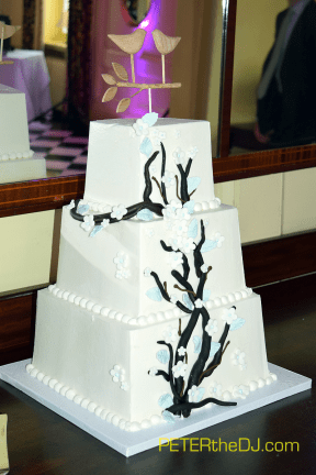 A close-up of the cake and the wooden-carved cake topper.