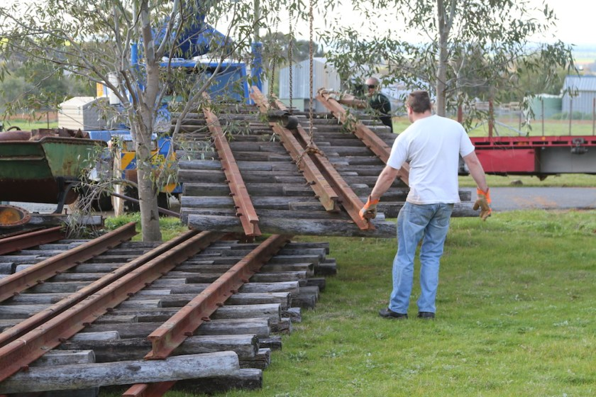 "2015.2073 – Having first unloaded the four passenger carriages ""over the fence"", the first lengths of ""set-track"" rails are unloaded. Ben guides them into a temporary storage location. 18th August 2015."