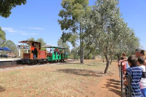 Image Joel 2424: With Ben at the controls, the Ruston hauls a loaded train through Loftus platform as some public enviously look on.