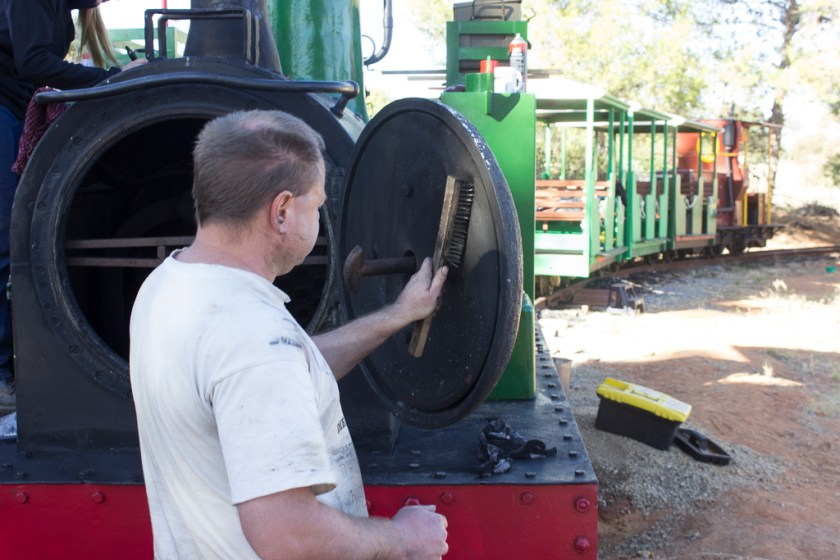 Image T0100: Meanwhile, Ben is down at the front end, wire-brushing the internal baffle of the smokebox door.