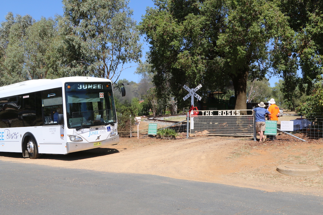"Image 2018.0387: Public transport around the Festival sites was for this year provided by Junee Buses who donated their services. This image shows Junee Buses making a stop outside Pete's Hobby Railway for a little bit of ""Train Spotting"""