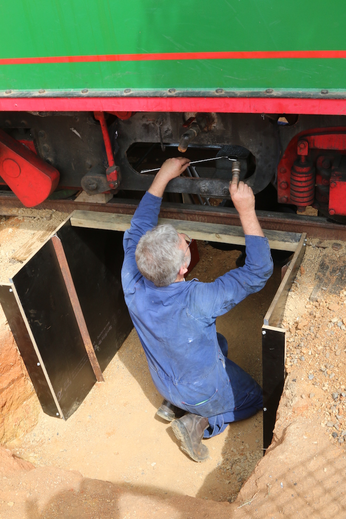 Image 2018.2786: Making full use of the newly completed temporary inspection pit, the Boiler Inspector is using a small torch and mirror to closely examine a washout plug at the rear of the firebox. Wednesday, 24th October 2018.