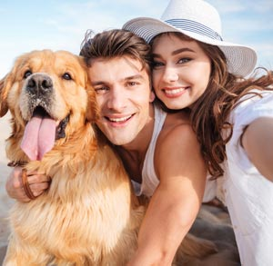 Picture of of a man and woman with their dog outside