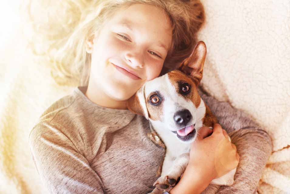 Picture of girl snuggling with at dog