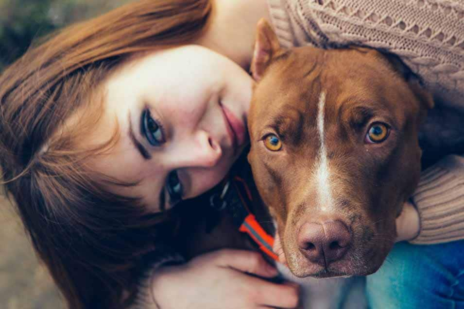 Picture of a young woman hugging a pit bull