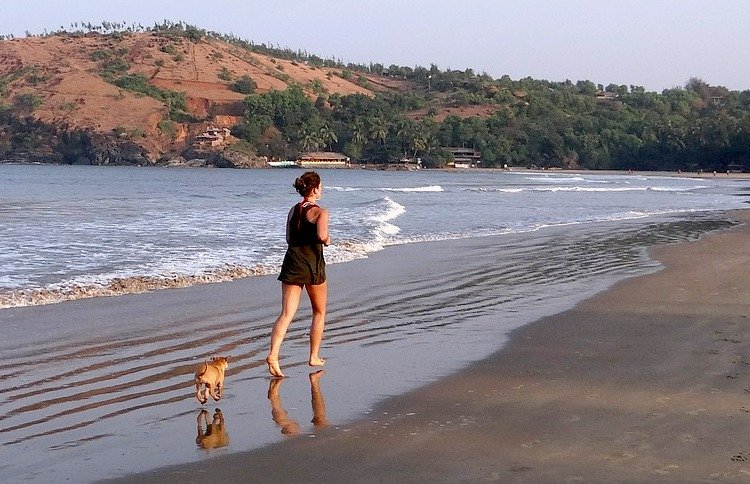 Photo of woman jogging with a puppy on a beach