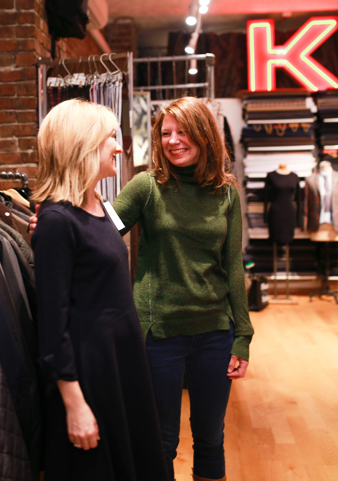 Sharing a giggle in a sweater dress and green sweater outfit at Kuhlman in Seattle.