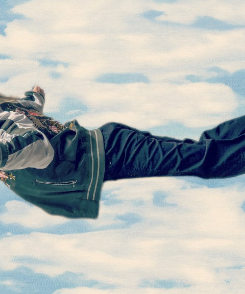 Woman in a jumpsuit and bomber jacket photoshopped to look like she's flying through clouds.