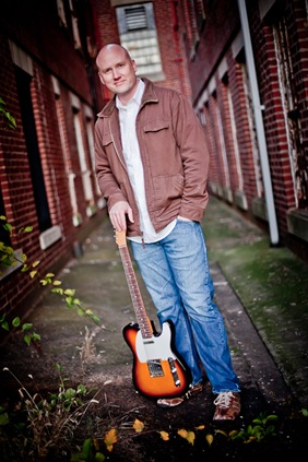 Randy Morser standing with his guitar
