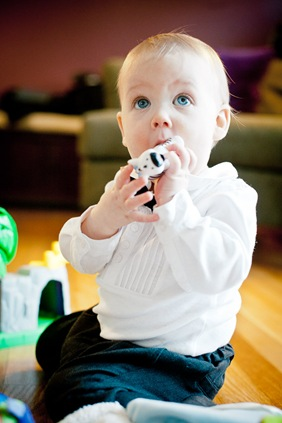 baby chewing on toy while sitting on the floor