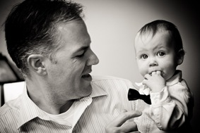 father holding baby while looking at the camera