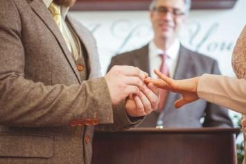 groom sliding a ring on the bride's finger
