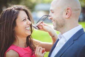 Woman takes sunglasses off her fiance's face.