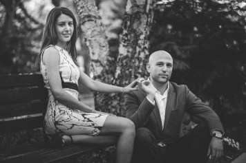 Black and white photo of engaged couple sitting on a bench in DC