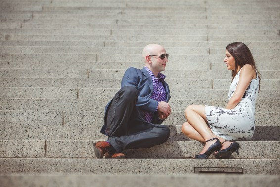 engaged couple having a discussion on the steps of the National Archives in DC