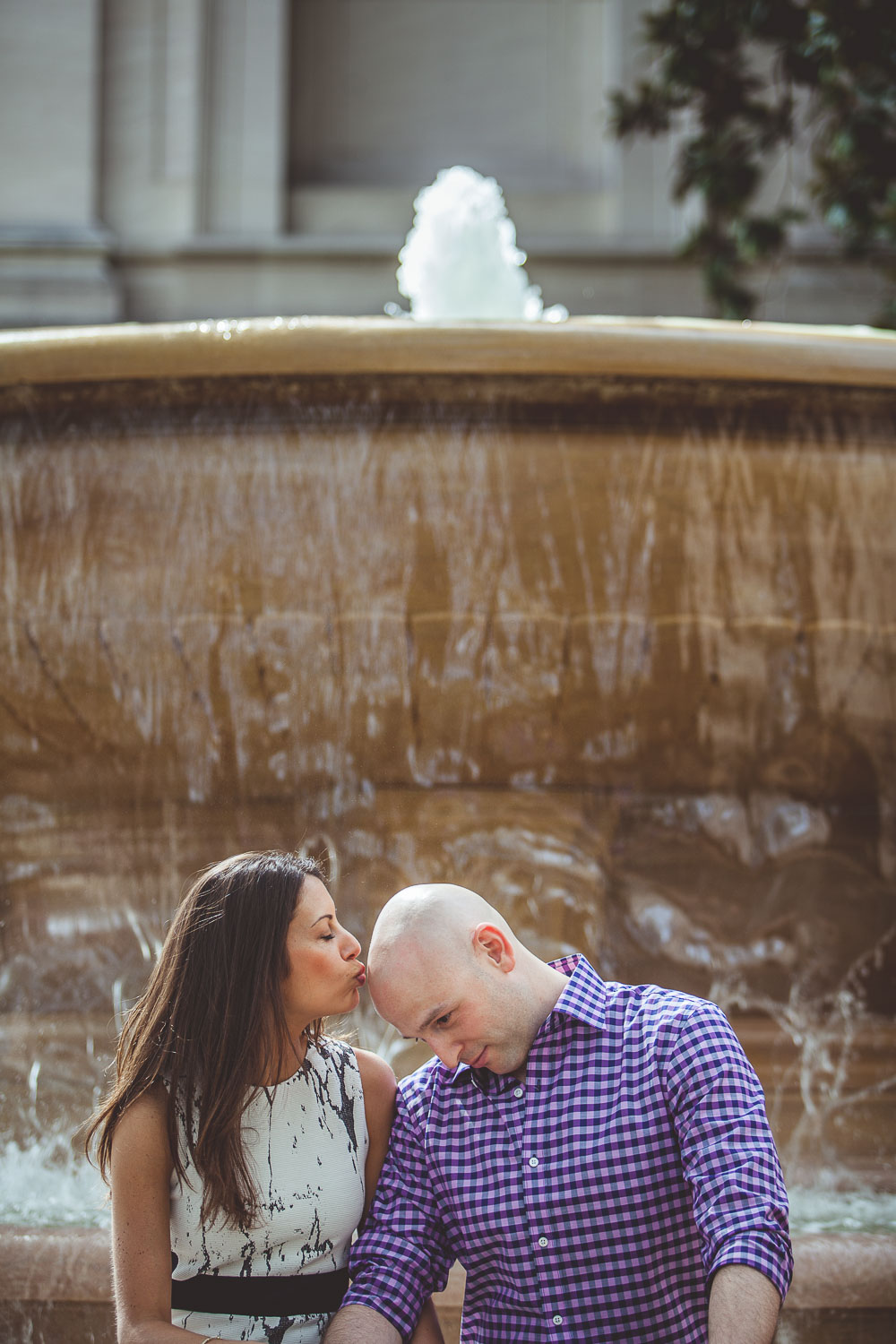 Black and white photo of an Engaged couple in front of a fountain in DC as she kisses his head.