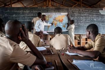 """Au CEG Hinvi, le long de la bruyante voie qui monte au nord, les moyens ne permettent pas de bâtir """"en dur"""". Les grandes salles faites de bois et de taule abritent plusieurs classes se jouxtant les unes les autres. Durant le cours d'histoire, il faut fréquemment aller chercher une des deux cartes dont dispose l'école afin que les élèves puissent suivre l'enseignant. // Hinvi - 2014"""