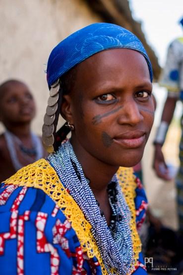 Comme le veut la tradition, les femmes Peules ont le visage tatoué (même la bouche chez certaines) et arborent de somptueuses parures en perles colorées.