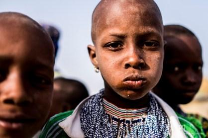 Tout comme les autres femmes de sa famille, cette jeune fille porte déjà une superbe parure de perles.