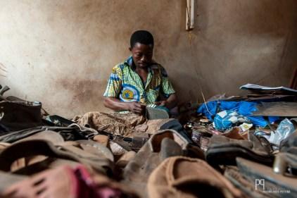 Caché derrière un monticule de chaussures hors d'usage, le cordonnier dépiaute soigneusement tout ce qu'il trouve afin réparer ce que lui apportent ses clients (savates, bottes de pluie, chaussures, etc.). // Allada - 2013