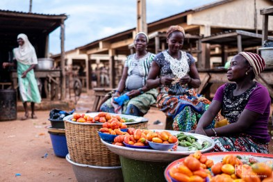 Vendeuses de tomates. Le marché ayant lieu tous les quatre jours, la grande place le long de la voie est quasiment déserte en dehors de ces moments d'effervescence. // Kérou - 2019
