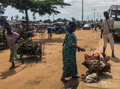 Sous un soleil de plomb, cette vendeuse arrose ses poules en attendant le taxi collectif qui l'amènera au marché. // Cocotomey - 2019