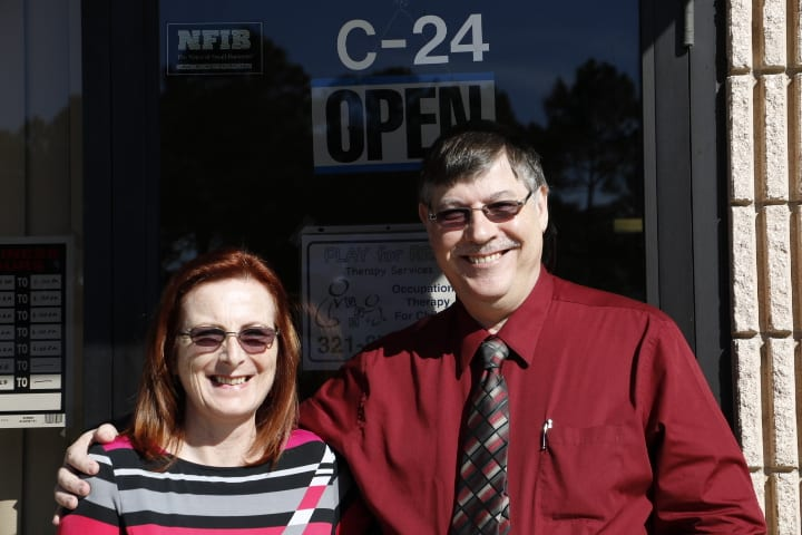 A picture of Peter and Lyn outside the Play for Real Therapy Clinic which opens today!