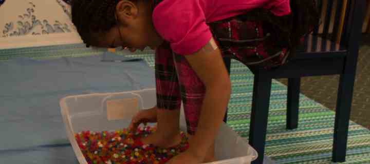 An image of a young client playing with water beads - Play for Real Pediatric Occupational Therapy