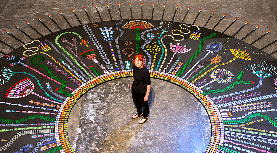 The artist Susie Freeman standing in the middle of a large circular piece with pills in the shapes of plants and flowers