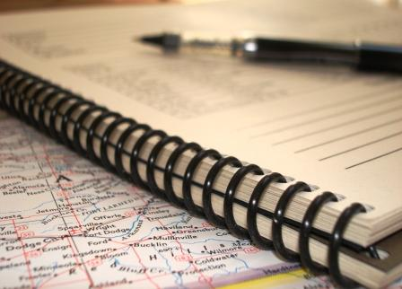 pen on a notebook and map