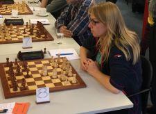 Schaakster Leonore Braggaar achter een schaakbord tegen de Westlandse Schaak Combinatie