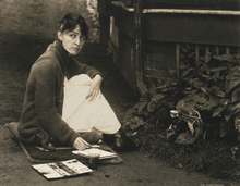 Alfred Stieglitz photograph of O'Keeffe with sketchpad and watercolors, 1918
