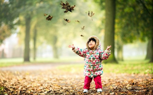 Happy-Child-Playing-With-Leaves-Wallpaper