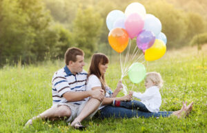 Mom, Dad, and baby with balloons