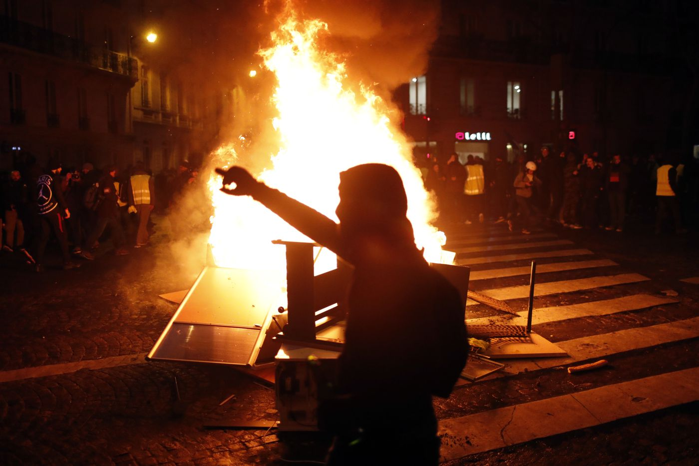 Demonstrators gather around a burning barricade during clashes with riot police in Paris on Saturday.
