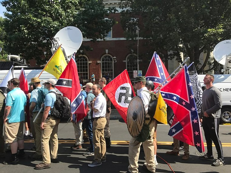 """Image from the Charlottesville """"Unite the Right"""" rally, featuring Confederate battle flags and Nazi swastika flags."""
