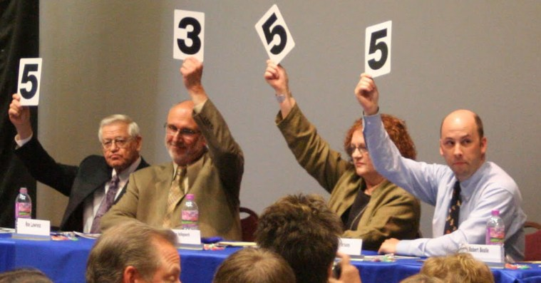 Judges scoring with numbers raised high.