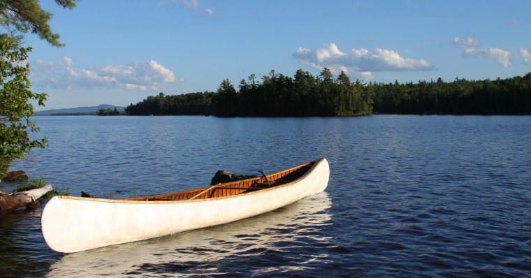 This is a photo of a canoe on a beautiful river in Maine with a blue sky above.