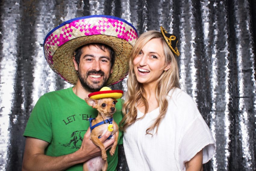 A couple and their small chihuahua wearing hats in the Culver City Photo Booth