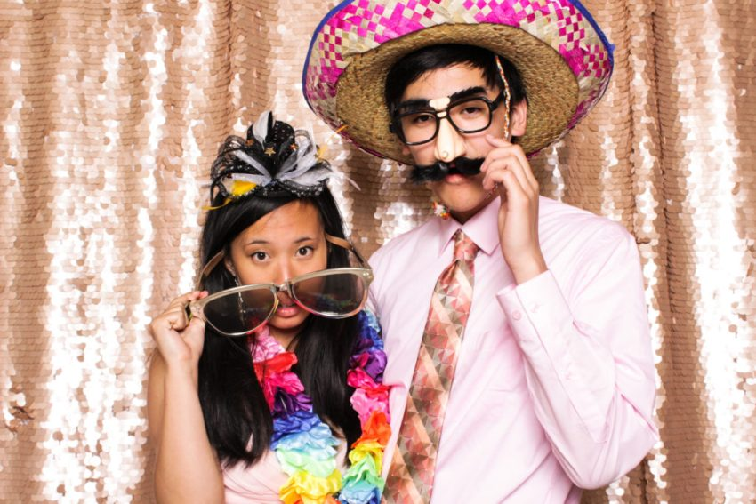 A girl looking over her oversized glasses next to a boy in a big sombrero and fake glasses in the Rancho Palos Verde Photo Booth