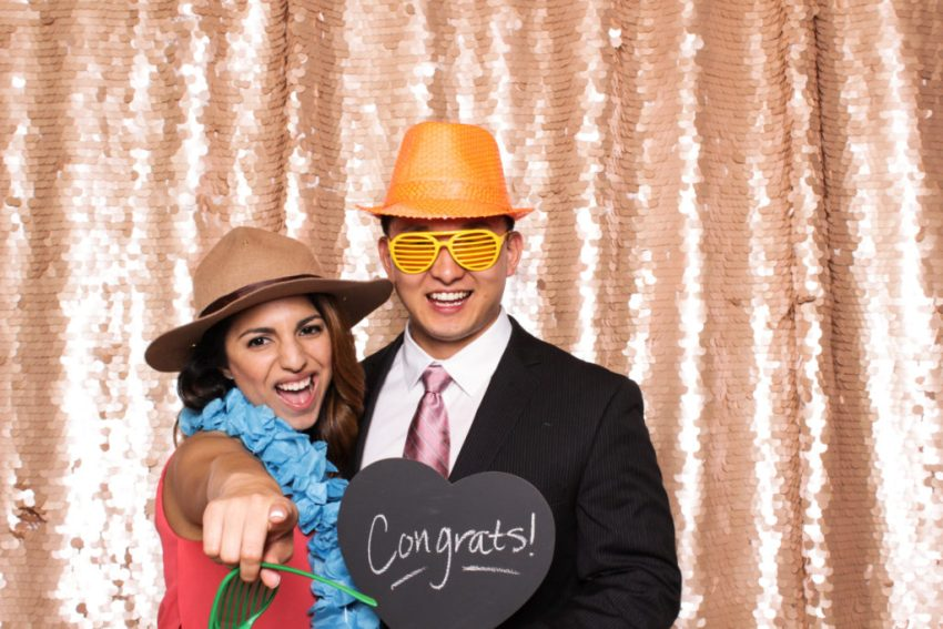 A girl and guy dressed up and holding a congratulations sign in the Rancho Palos Verde Photo Booth
