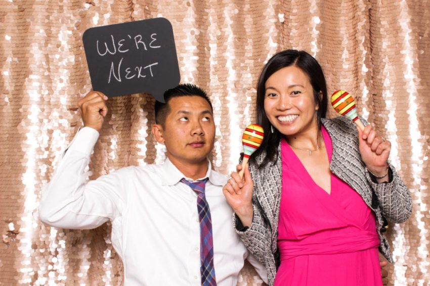 An excited couple holding a 'We're next' sign in the Rancho Palos Verde Photo Booth