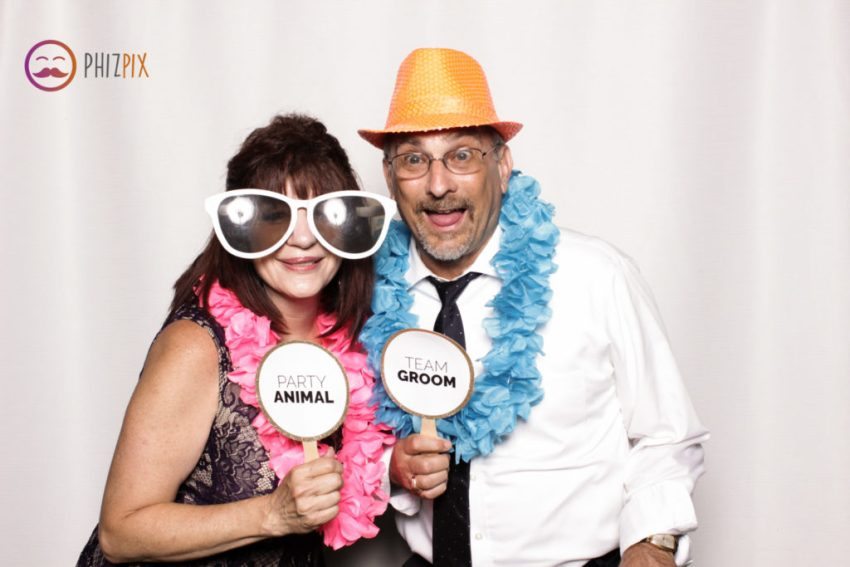 A couple in feather boas, holding 'Party Animal' and 'Team Groom' signs in the Malibu photo booth