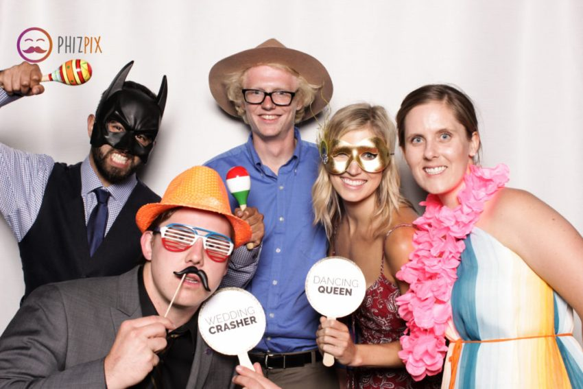 Five friends, all with props, smiling in the Malibu photo booth