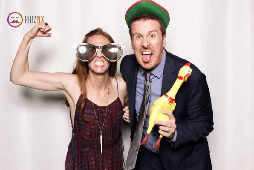 A girl, a guy and a rubber chicken posing in the Malibu photo booth