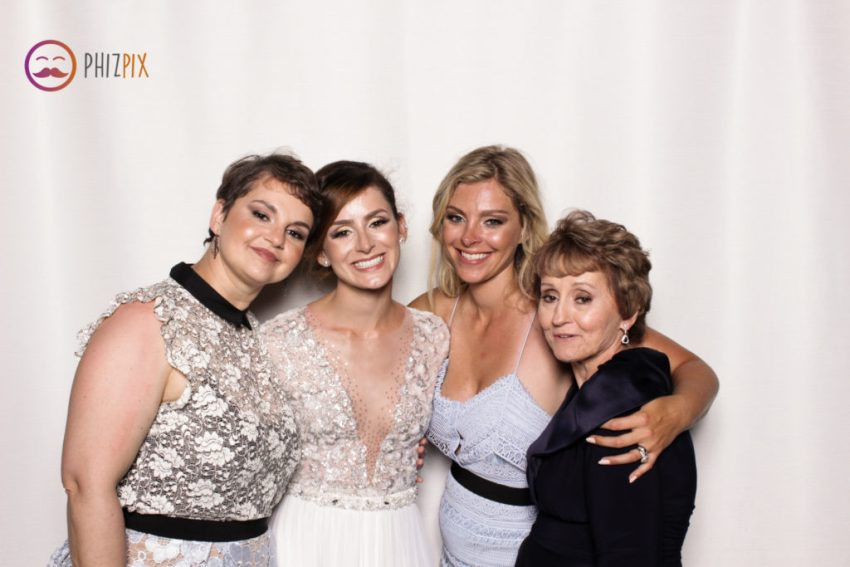 The beautiful bride, her two sisters and mother smiling and hugging in the Malibu photo booth